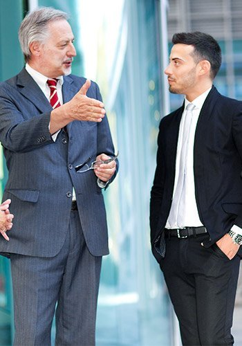 Two business men talking outside in a city